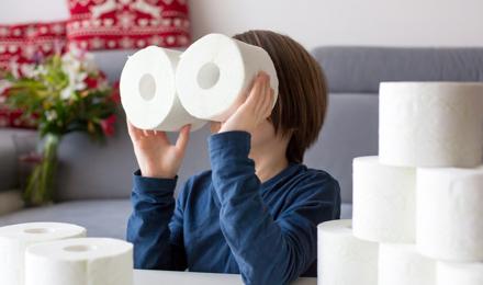 Egy gyermek toalettpapír-gurigákkal játszik