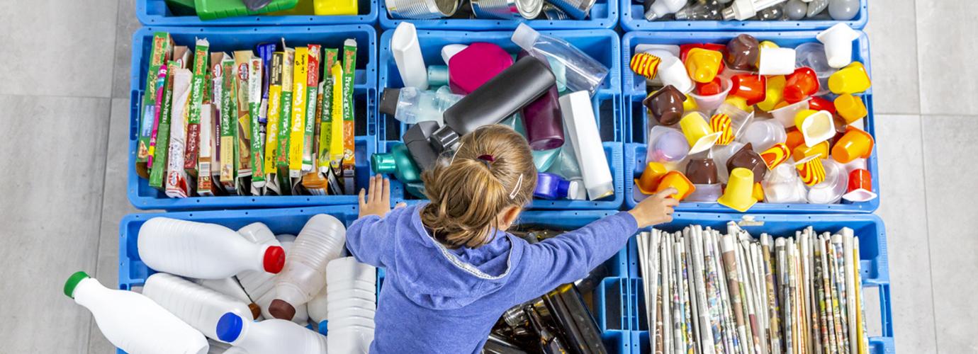 Egy gyermek válogat az újrahasznosításhoz otthon